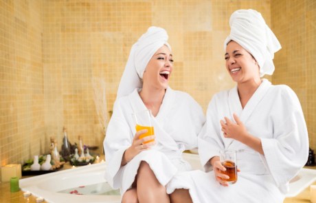 Two ladies wearing white dressing gowns and towels in spa